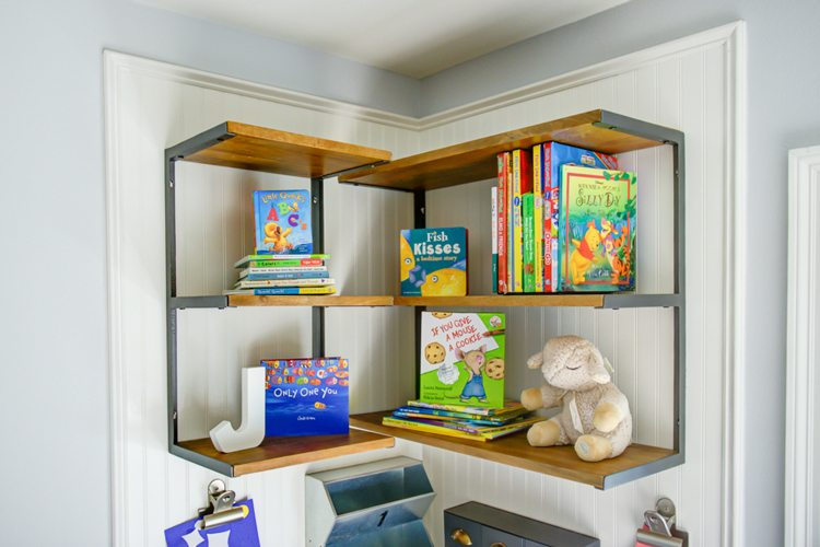 loving this coastal surf shack toddler boy room. the surf board above the crib is my favorite. nursery also features a reading nook art corner.