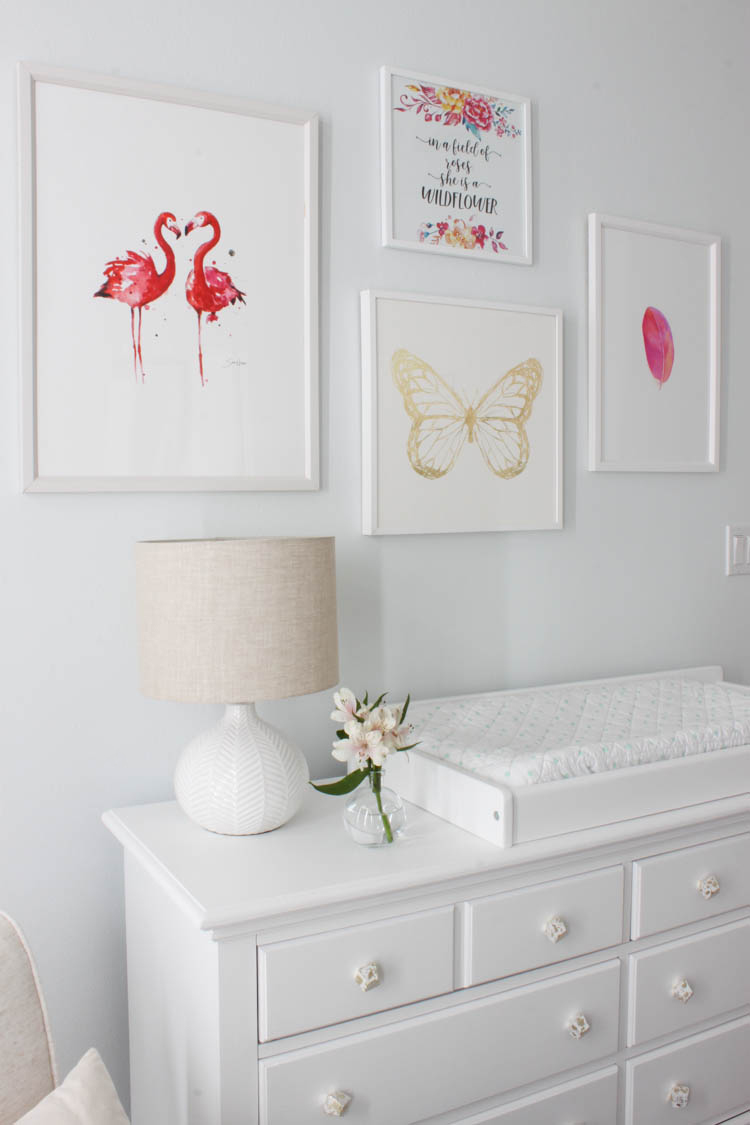 a beautiful, whimsical, magical baby girl nursery featuring a polka dot ceiling, lotus chandelier, unicorn, pink flamingos, penguins, and gold butterfly fit for a little wildflower